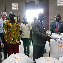 Honourable Vincent Ssempijja, Minister of Agriculture, Animal Industry and Fisheries; Honourable Earnest Kiiza, Minister of State for Bunyoro Affairs posing with a bag of feed